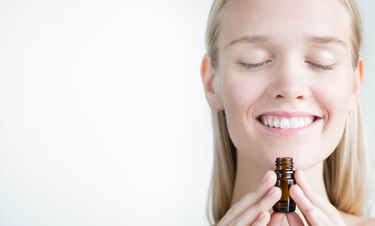 Woman enjoying the scent of an essential oil bottle