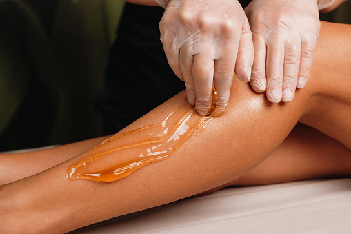 Close up photo of a sugaring on legs procedure done by a experienced specialist in spa